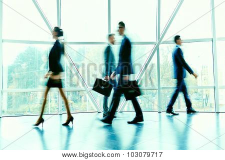 Blurred figures of hurrying employees inside office building