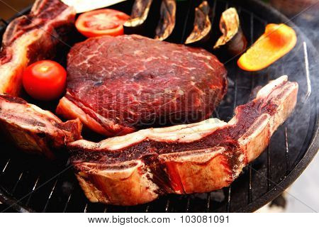 fresh raw beef meat fillet and asado ribs with vegetables prepared on deep charcoal bbq grill