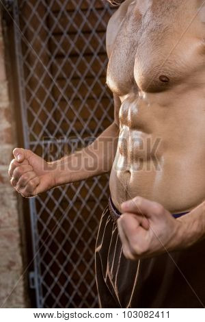 Midsection of man with clenched fist at the gym