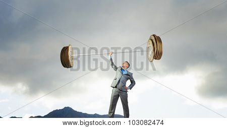 Confident businessman lifting above head barbell made of coins