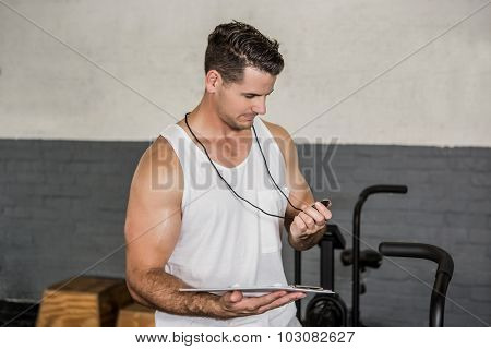 Instructor holding stopwatch and clipboard at the gym