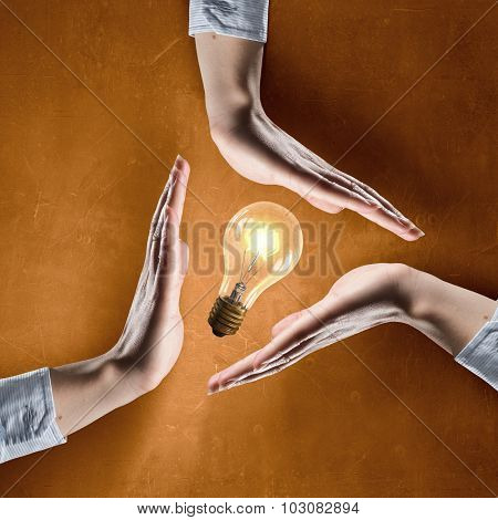 Close up of hands covering glowing light bulb