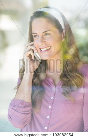 Happy woman talking on cellphone by window at home