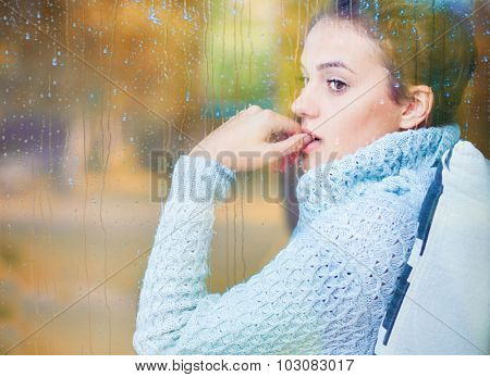 Thoughtful beautiful young brunette woman sitting behind a window covered with rain drops. Blurred autumn garden reflection on the glass