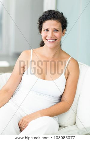 Portrait of happy pregnant woman sitting on lounge sofa at home