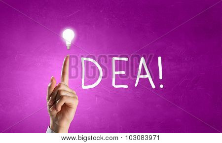 Close up of hand pointing with finger at light bulb