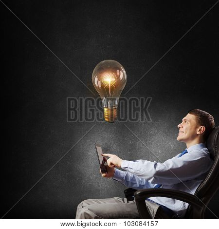Young businessman in armchair using tablet pc looking at glass lightbulb
