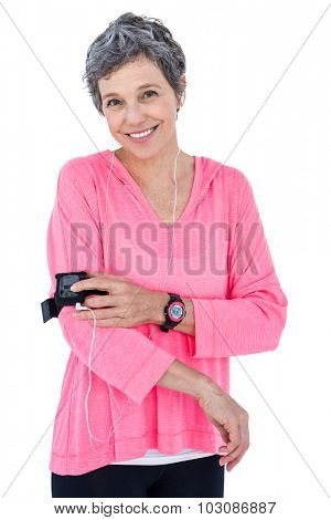 Portrait of happy woman using mp3 player in armband against white background