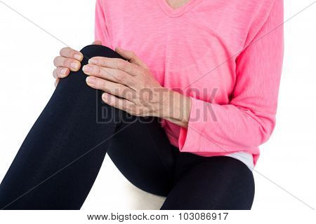 Mid section of mature woman massaging knee while sitting against white background