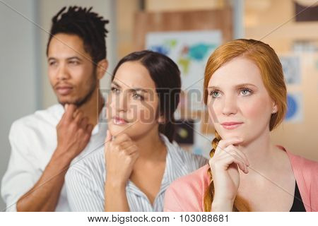 Business people thinking with hands on chin and looking away at office