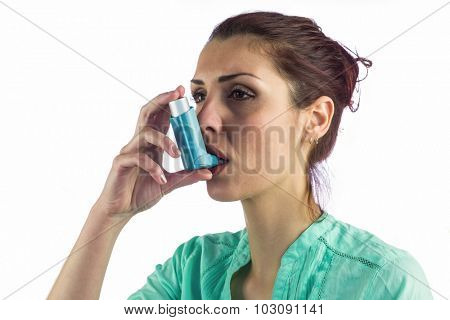Close-up of woman using asthma inhaler against white background