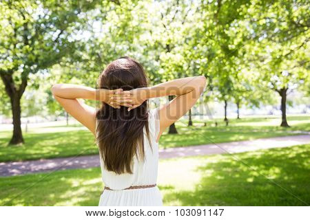 Rear view of long hair woman with hands behind head while standing in park