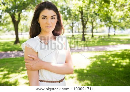 Portrait of confident woman standing on grassland in park