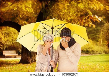 Couple sneezing in tissue while standing under umbrella against trees and meadow in the park