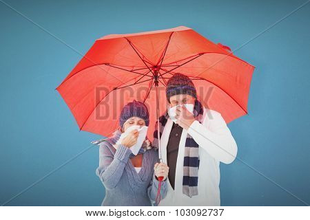 Mature couple blowing their noses under umbrella against blue background