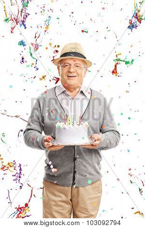 Vertical shot of a joyful senior gentleman carrying a birthday cake with party streamers flying all around him isolated on white background