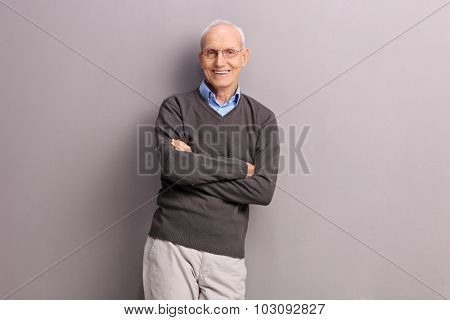 Cheerful senior gentleman leaning against a gray wall and looking at the camera