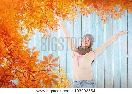 Smiling brunette standing arms open against autumn leaves pattern