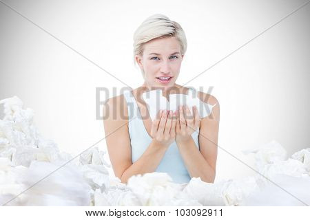 Sick woman holding tissues looking at camera against white background with vignette