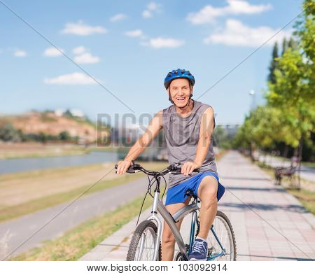 Cheerful senior man in sportswear posing with his bike on a sidewalk and looking at the camera shot with tilt and shift lens