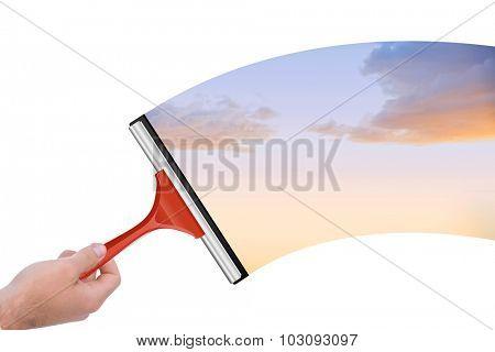 Hand using wiper against beautiful orange and blue sky