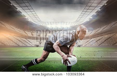 Determined athlete bending while playing rugby against rugby arena