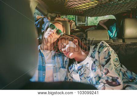 Tired women friends sleeping in a rear seat car