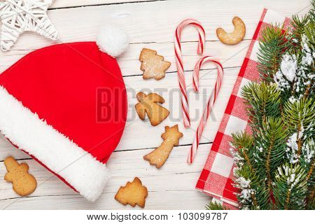 Christmas santa hat, gingerbread cookies and snow fir tree. View from above over white wooden table background