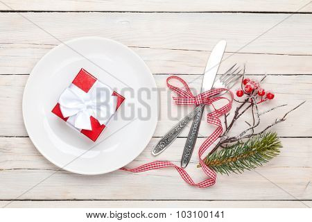 Gift box on plate, silverware and christmas decor. View from above over white wooden table background