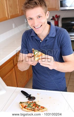 Young man in the kitchen enjoying pizza