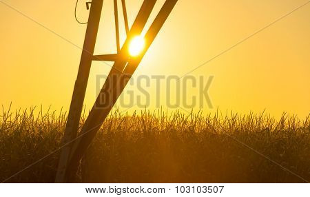Tower of a power line in a yellow sky at sunrise