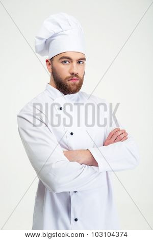 Portrait of a serious male chef cook standing with arms folded isolated on a white background and looking at camera