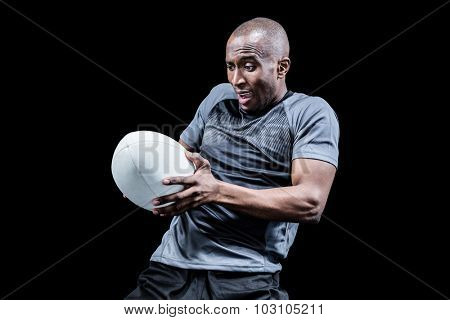 Sportsman catching rugby ball while playing against black background