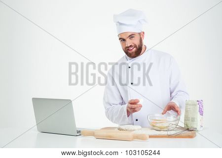 Portrait of a happy male chef cook baking with laptop isolated on a white background