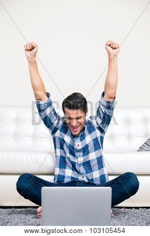 Portrait of excited man sitting on the floor and watching the game on laptop at home