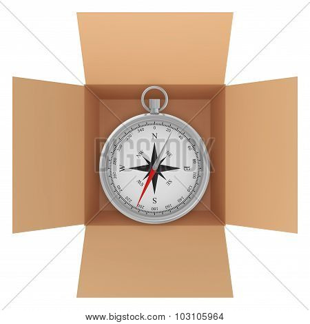 Metal compass with wind rose inside a cardboard box