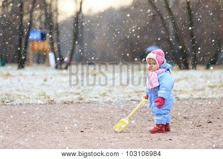 little girl play in snow winter park