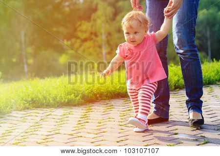 first steps of little girl with mother outdoors