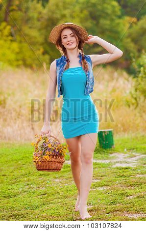 Young girl in a straw hat with a basket of wild flowers