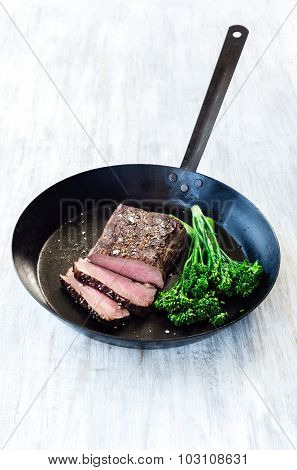 Medium cooked steak on a cast iron pan with fresh green vegetables