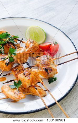 Close up of chicken kebabs served with tomatoes lime and coriander in a rustic enamel plate