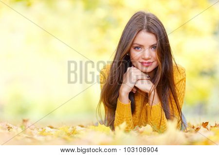 Portrait of a beautiful young brunette woman laying in the autumn park