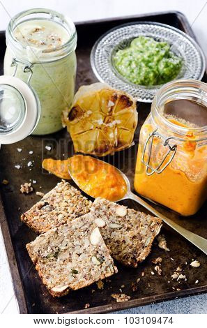 Variety of dips and spreads, creamy mustard, roasted tomato and red pepper, pesto, roasted garlic with healthy seeded bread as a snack platter for a party
