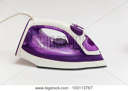 Purple Iron For Ironing On A White Background