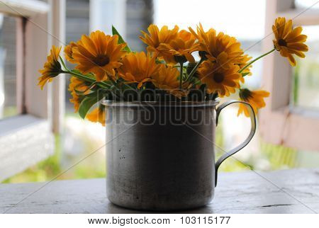 Yellow flowers in the iron mug