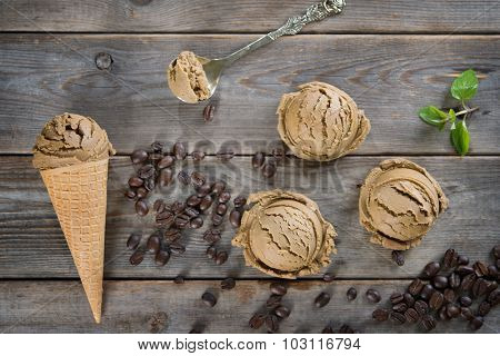 Top view mocha ice cream in waffle cone and coffee beans on old rustic vintage wooden background.