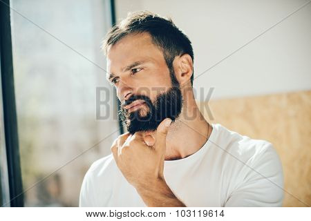Portrait of a bearded man wearing white tshirt and looking