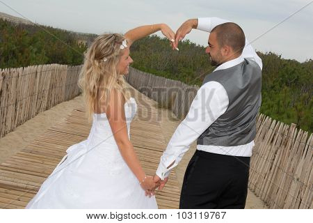 Young Wedding Couple Make A Heart With Arms