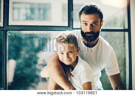 Portrait of a bearded man and his son near the window