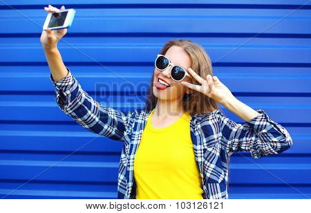 Fashion Pretty Woman In Colorful Clothes Having Fun Makes Self-portrait On The Smartphone Over Blue